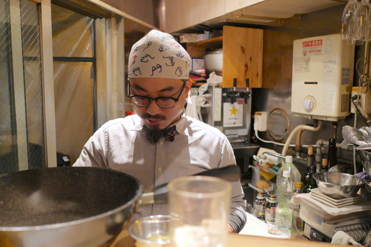 Looking KANDA NAMBAR's owner over the shoulder as he is cooking in his tiny kitchen